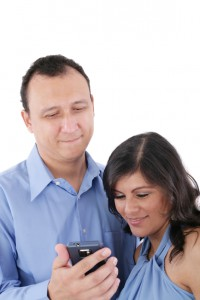 Couple looking at a cell phone and smiling isolated on a white background